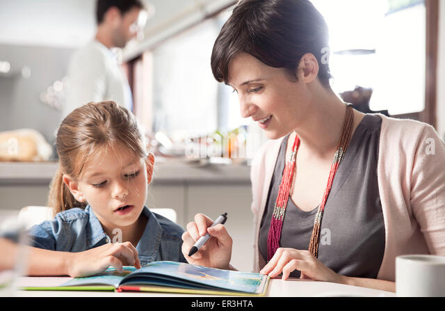 Mother and young daughter reading together - Stock Image