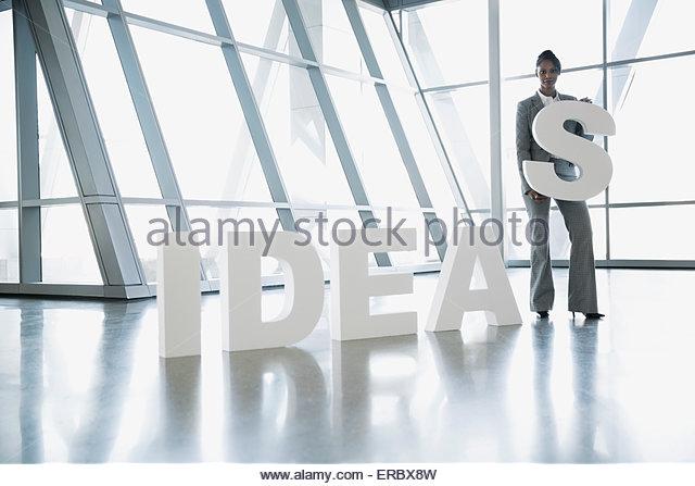 Portrait businesswoman holding letter S in 'Ideas' - Stock Image