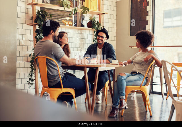 Young people sitting at a cafe table. Group of friends talking in a coffee shop. - Stock Image
