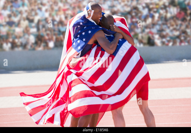 Track and field athletes wrapped in American flag on track - Stock Image