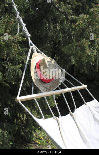 Hammock and strawhat in garden - Stock Image