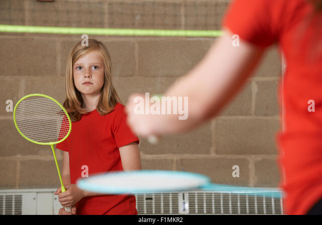 Two Girl Playing Badminton In School Gym - Stock Image