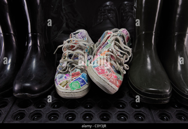 Running shoes covered with postage stamps, among dark and black rubber boots and black shoes. - Stock Image