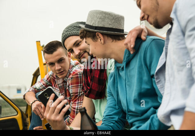 Group of friends with cell phone on pick-up truck - Stock Image