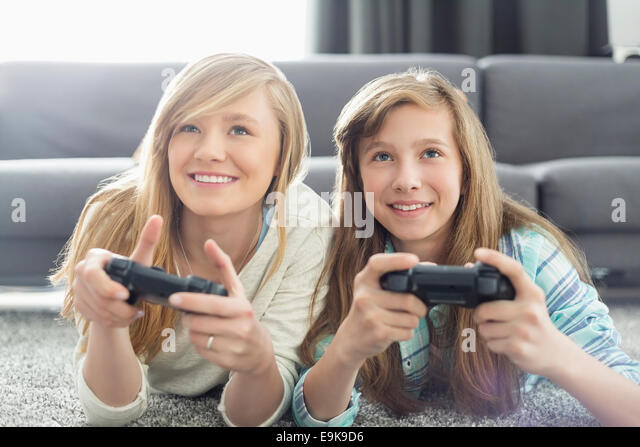 Sisters playing video games in living room - Stock Image