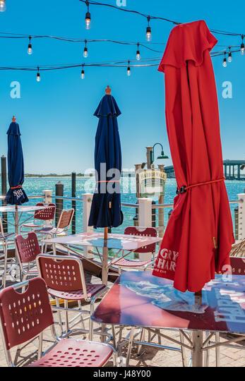 Closed patio table umbrellas waiting for diners at Harbor Walk Marina, Destin, Florida. - Stock Image