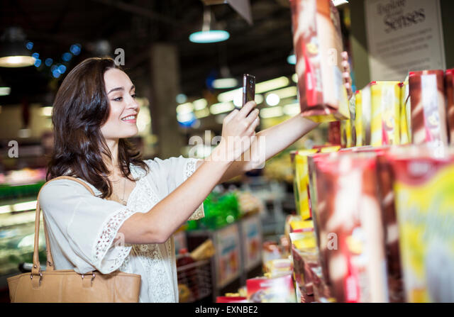 Woman at supermarket scanning prices with her smart phone - Stock Image