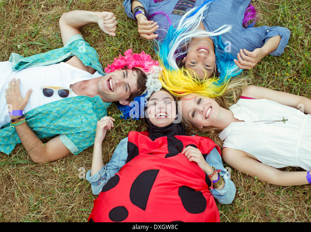 Portrait of friends in costumes laying in grass at music festival - Stock Image