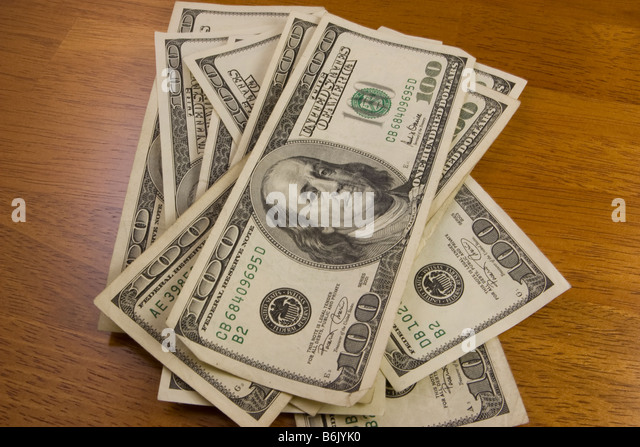 100 dollar bills on table