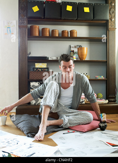 Mid adult man looking at sketches and artwork on floor - Stock Image