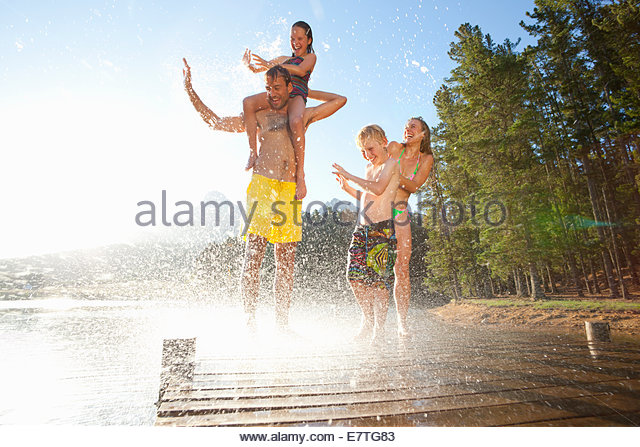 Water splashing on family on wooden dock at lake - Stock Image