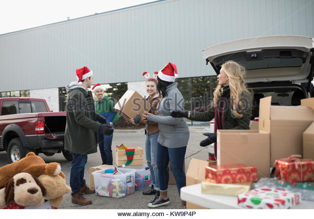 Young adult volunteers in Santa hats sorting Christmas donations in parking lot - Stock Image