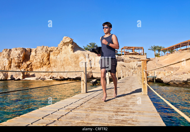 Snorkeler carrying fins on wooden pier - Stock-Bilder