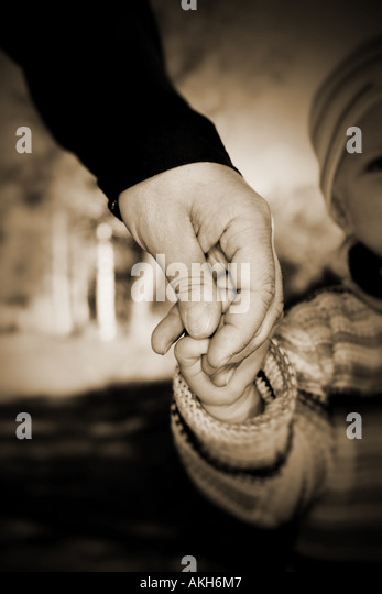 Guidance through the world Holding hand of a child to guide it - Stock-Bilder
