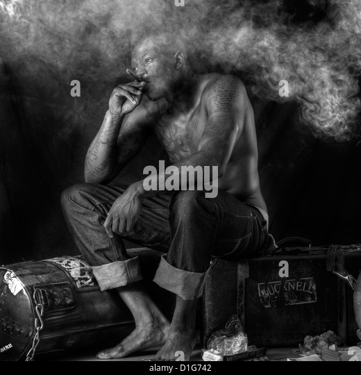 Athelete/boxer taking a rest smoking a cigar - Stock Image