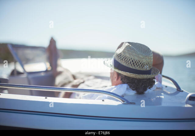 Older man relaxing in boat on water - Stock Image
