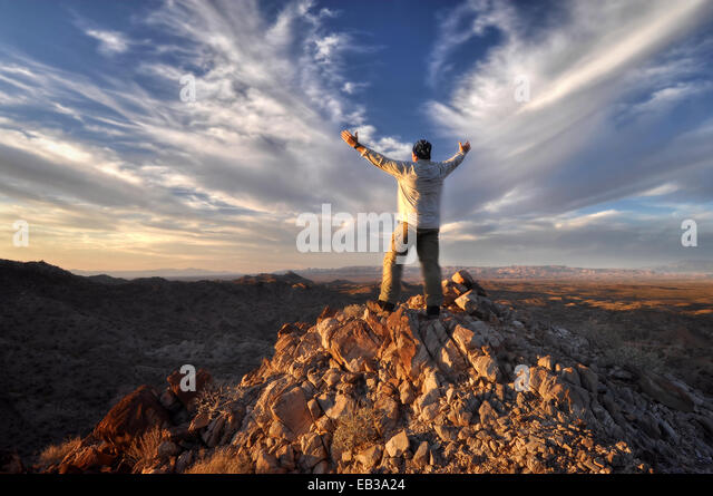 USA, Arizona, The Needles, Windy Mountain, Man raising arms on mountaintop - Stock Image