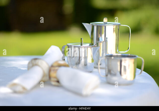 Luxury silver coffee pot on a linen covered table outside in summer. - Stock Image