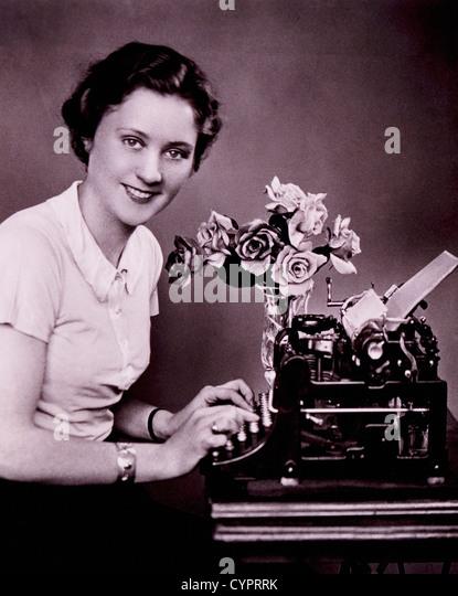 Smiling Woman Typing on Typewriter, Circa 1930's - Stock Image
