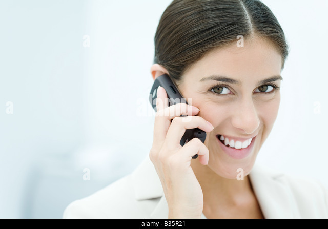 Young woman talking on cell phone, smiling at camera, portrait - Stock-Bilder