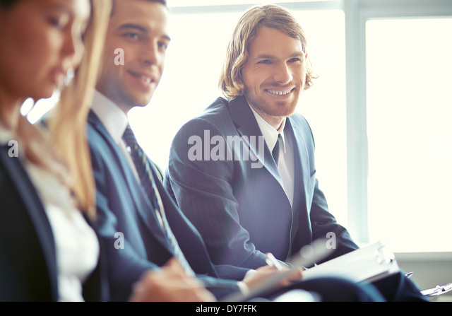 Row of business people sitting at seminar with focus on smiling young man - Stock Image