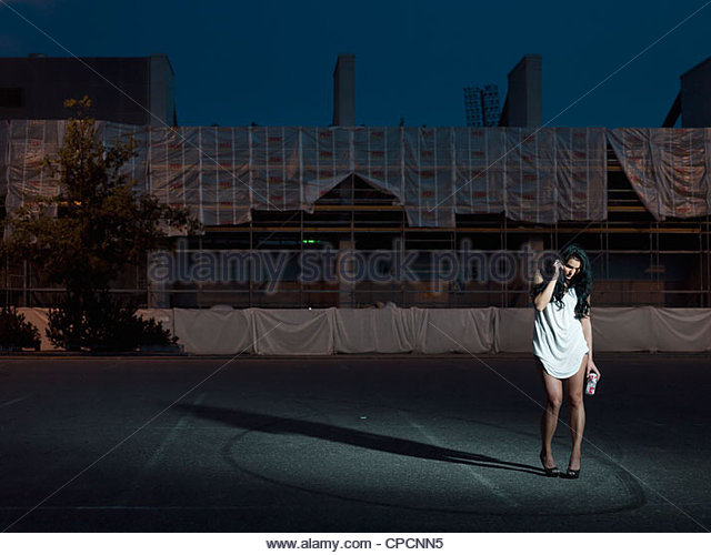 Woman walking in city at night - Stock-Bilder