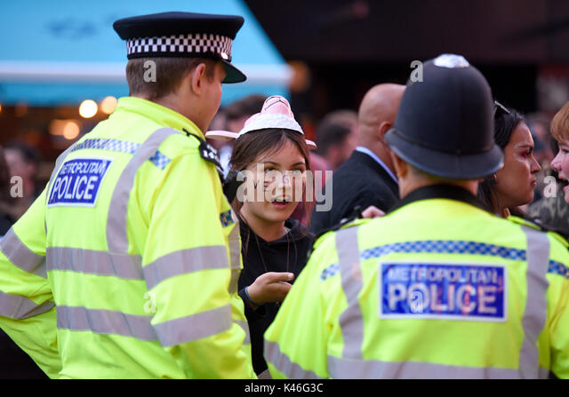 Metropolitan police asking a vegan animal rights activist to move along in Leicester Square, London. Space for copy - Stock Image
