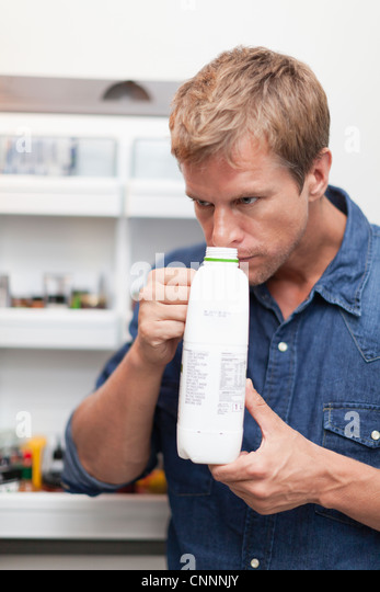 Man smelling milk jug for freshness - Stock Image