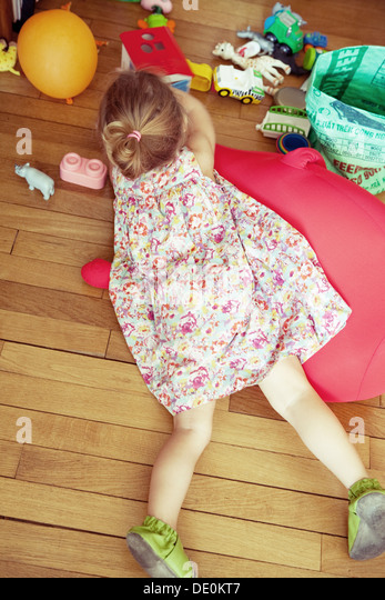 Little girl lying on floor with toys, overhead view - Stock Image