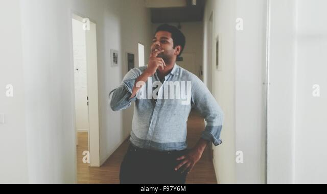 Man Thinking While Standing In Corridor At Home - Stock Image