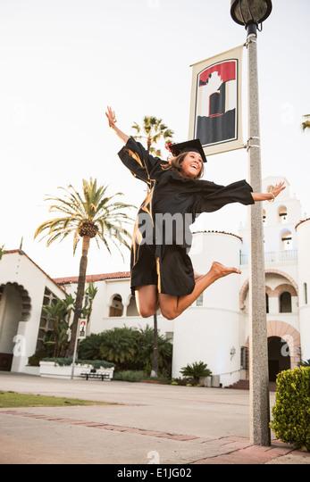 Female graduate jumping for joy - Stock Image