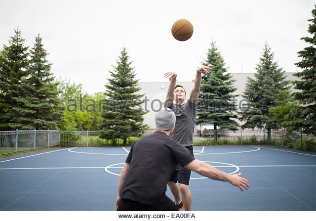 Young men playing basketball - Stock Image