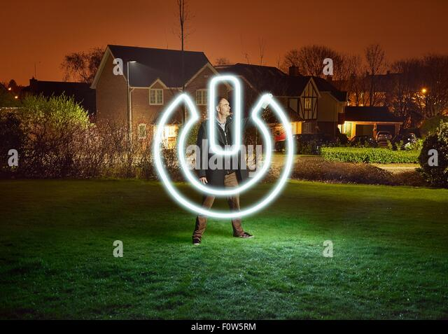 Artist light painting a power switch symbol in park - Stock Image