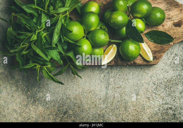Fresh limes and mint on board for making summer drinks - Stock Image