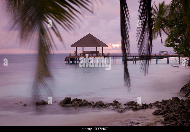 Dusk setting behind landing stage on tropical resort in Maldives near India - Stock-Bilder