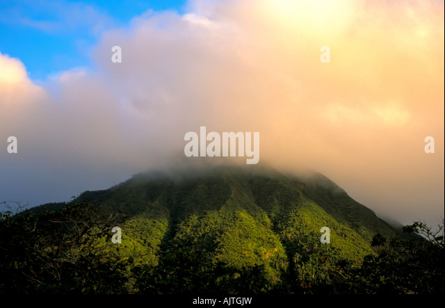 Mount Nevis peak, green volcano peak, Caribbean, leeward islands, cloud cover at the top, blue sky background, national - Stock Image