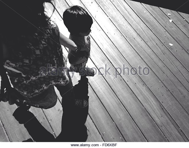 Low Section Of Mother With Child Walking On Hardwood Floor - Stock Image