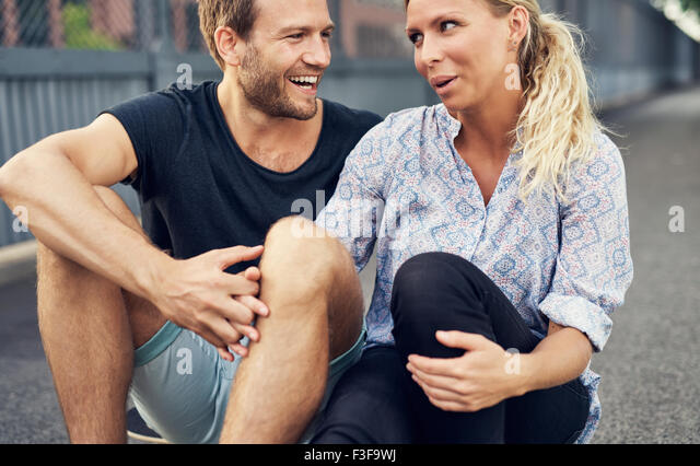 Couple having a good time while sitting on the ground - Stock-Bilder