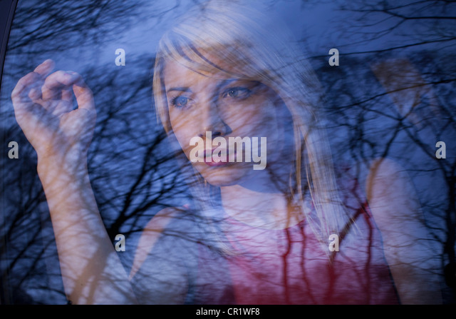 Woman peering out car window in woods - Stock Image