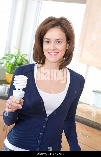 Woman holding energy efficient compact fluorescent  bulb, Winnipeg, Canada - Stock Image