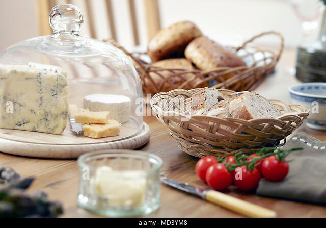 Table with fresh bread, cheeses and vine tomatoes - Stock Image