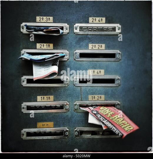 Building letterboxes full of junk mail in Barcelona, Catalonia, Spain - Stock Image