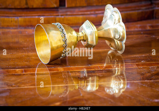 Golden grail turned on wooden background - Stock Image