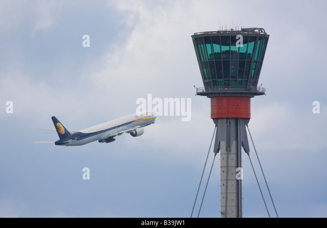 Jet Airways Boeing 777-35R/ER taking off in the background of London Heathrow control tower. - Stock Image