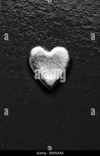 Gold heart shape against textured metal background. Monochrome - Stock Image