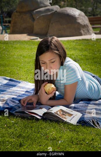 12 -13 year years old mixed race Vietnamese/Caucasian girl eating apple reading on grass park. MR  © Myrleen - Stock-Bilder