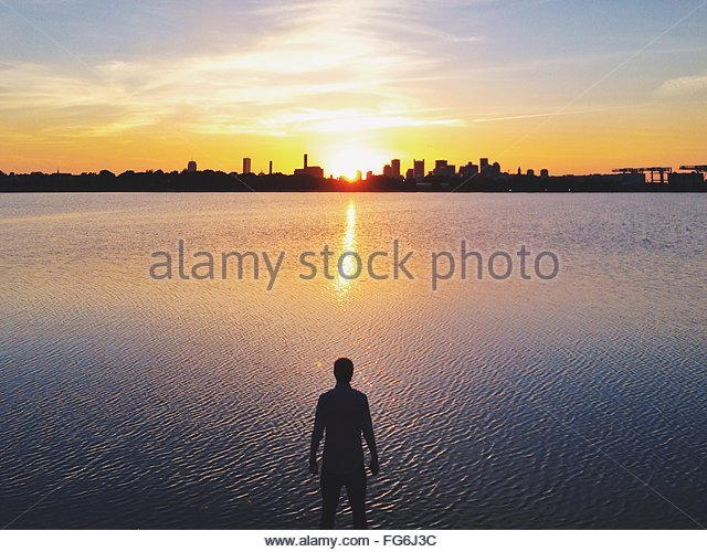 Silhouette Man Standing By River And City Against Sky At Sunset - Stock Image