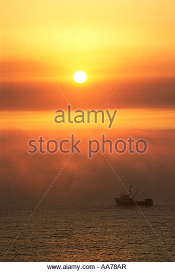 A fishing boat crosses the horizon, silhouetted by the setting sun, Oregon coast. - Stock Image