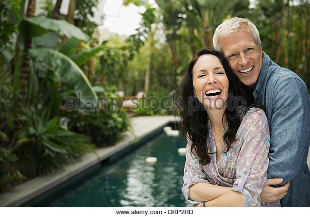 Portrait of affectionate couple embracing outdoors - Stock Image