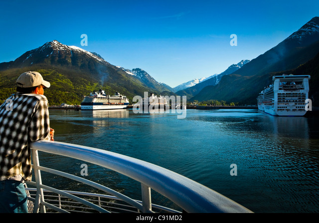 An Alaska Marine Highway ferry passenger looking at the port of Skagway crowded with four moored cruiseships, Southeast - Stock Image